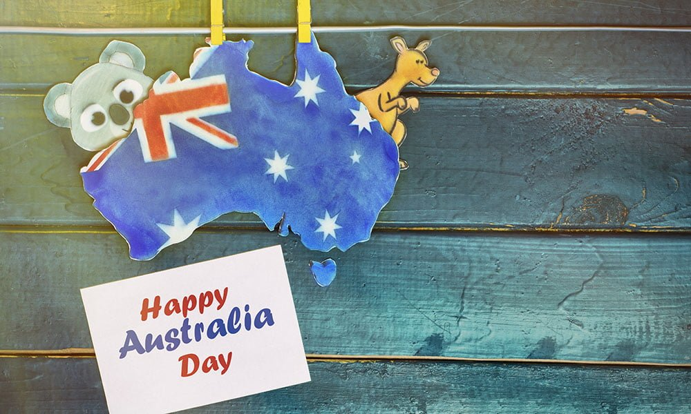 Australia Day holiday on January 26. Concept - Happy Australia Day message greeting written across white white hearts holding by kangaroos and koala, hanging pegs. toned image. sunlight effect