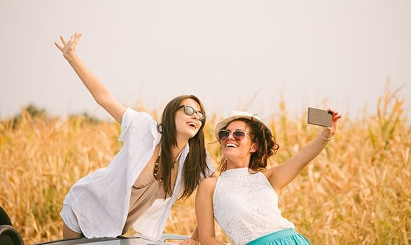 Two female friends beside cabriolet taking selfies with smartpho