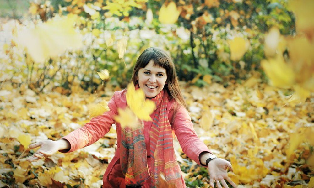 The young happy woman in autumn park