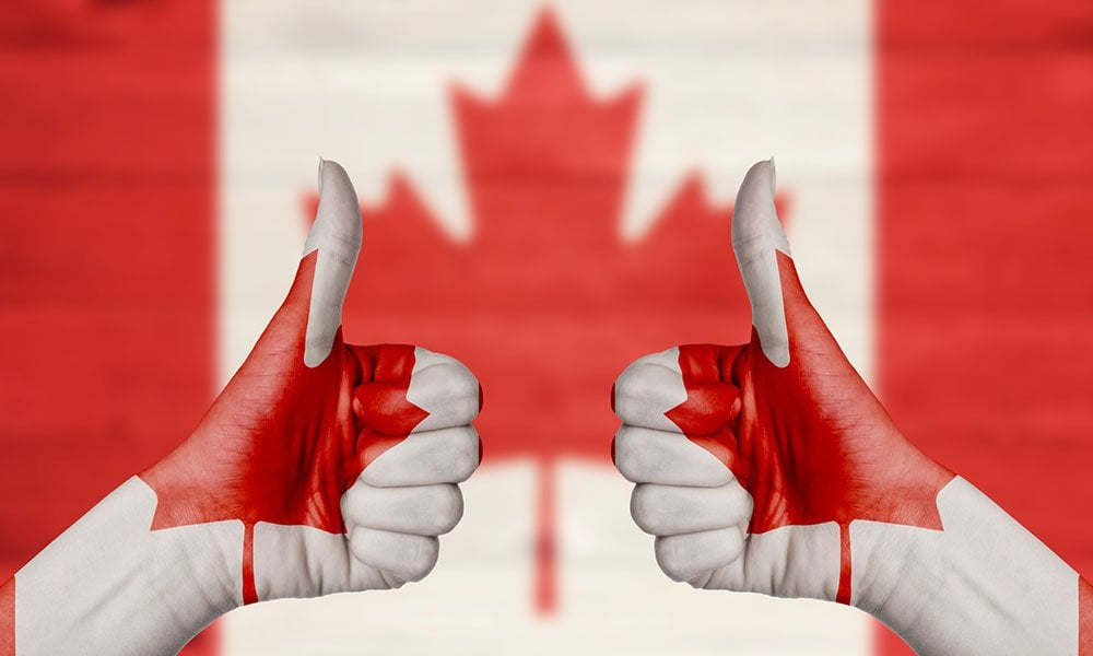 Canada flag painted on female hands thumbs up with blurry wooden background